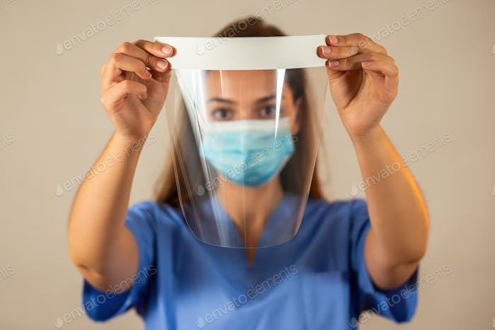 Female nurse in blue shirt holding protective face shield in front of her