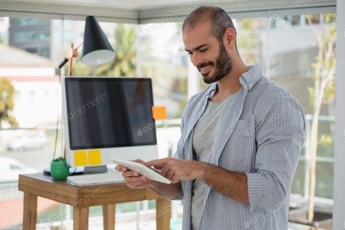 Smiling designer using digital tablet in office