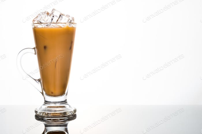 Refreshing ice cold coffee with milk in transparent glass