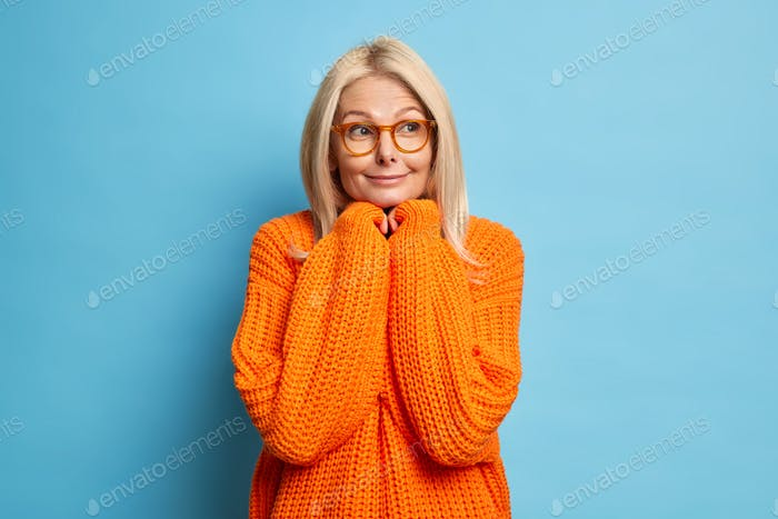 Beautiful blonde thoughtful middle aged woman keeps hands under chin and thinks deeply about somethi