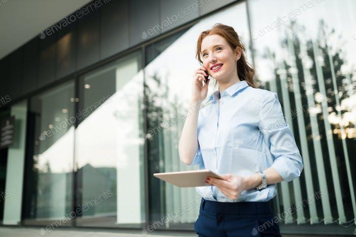 Geschäftsfrau spricht Handy während eines Arbeitstages