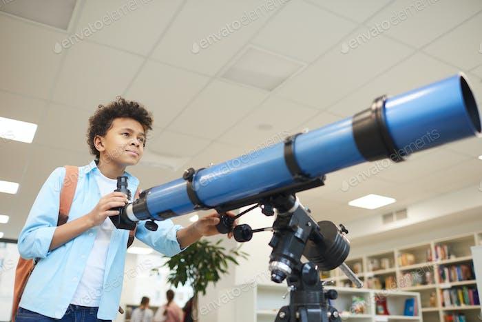 Афро-американский мальчик с телескопом