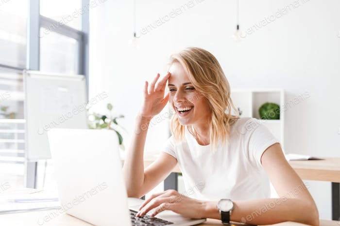 Happy businesswoman working on laptop computer