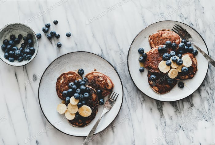 Breakfast with banana pancakes with bluelerry and honey in plates