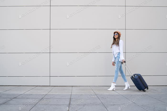 Young woman carrying a suitcase outdoors.