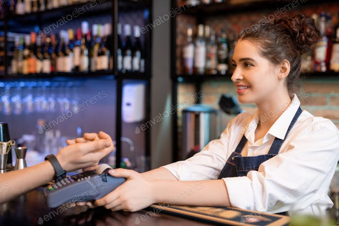 Happy young waitress holding payment machine over counter