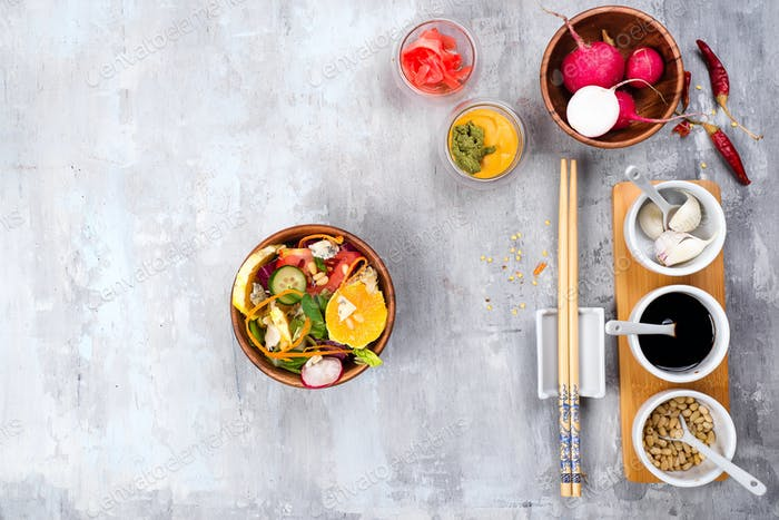 Spring Salad with fine Chinese noddles and red radish on stone background