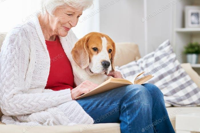 Liebevolle Senior Frau Lesen mit Hund