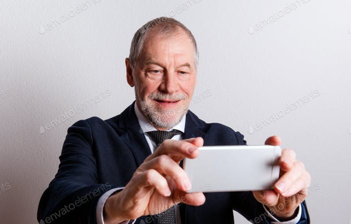 Portrait of a senior man with smartphone in a studio, taking selfie.