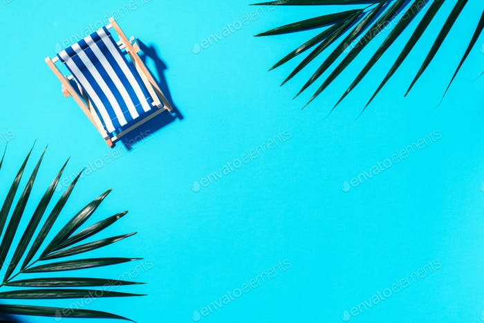 Deck chair with hard shadow, palm leaves on blue paper background. Flat lay and copy space. Summer