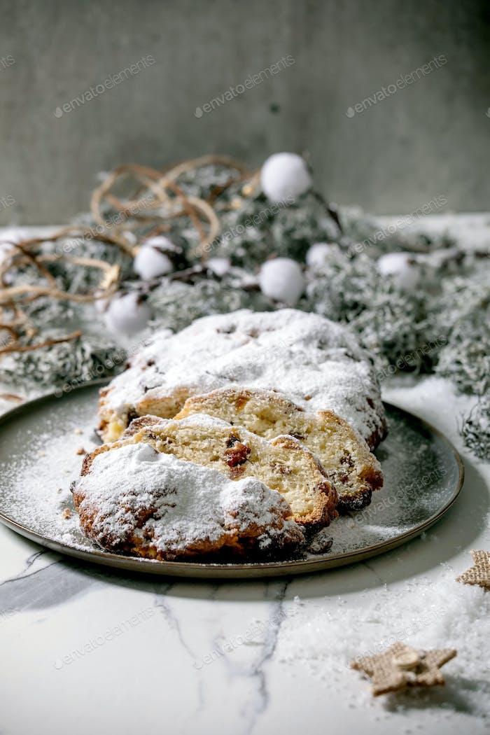 Weihnachtsbäckerei Stollenkuchen mit Weihnachtsdekorationen über weißem Marmor