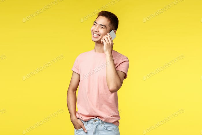 Technology, communication and lifestyle concept. Portrait of cheerful asian male in pink t-shirt