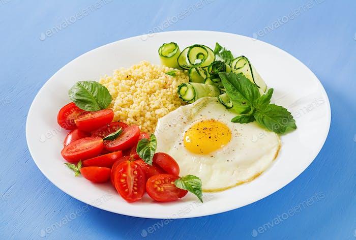 Healthy breakfast. Dietary menu. Millet porridge and tomato, cucumber salad and fried eggs.