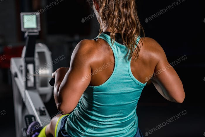 Woman athlete exercising on rowing machine
