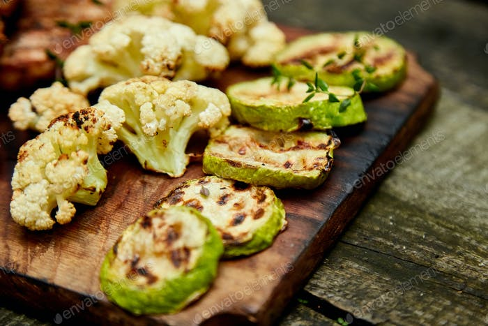 Grilled zucchini and cauliflower vegetable on wooden background .