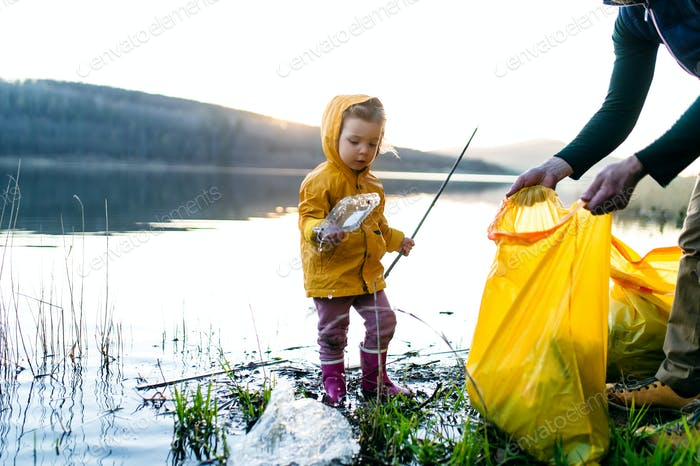 Father with small daughter collecting rubbish outdoors in nature, plogging concept