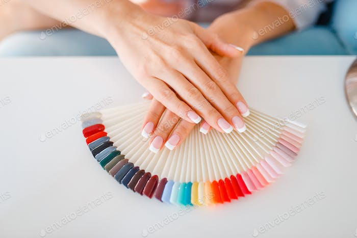 Female hands and colorful nail varnish palette