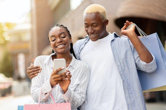 Senden von Werbung an Smartphone. Glückliches Paar mit Einkaufstaschen Blick auf Telefon