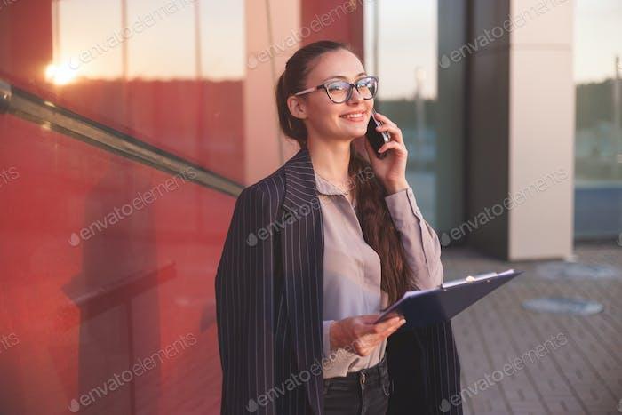 Geschäftsfrau mit Dokumenten telefoniert