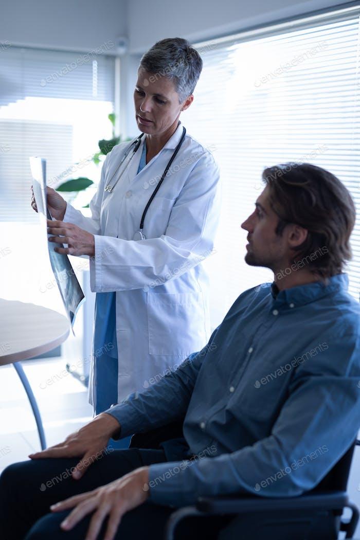Reife Ärztin zeigt Röntgenbericht für behinderte Patienten in Klinik im Krankenhaus