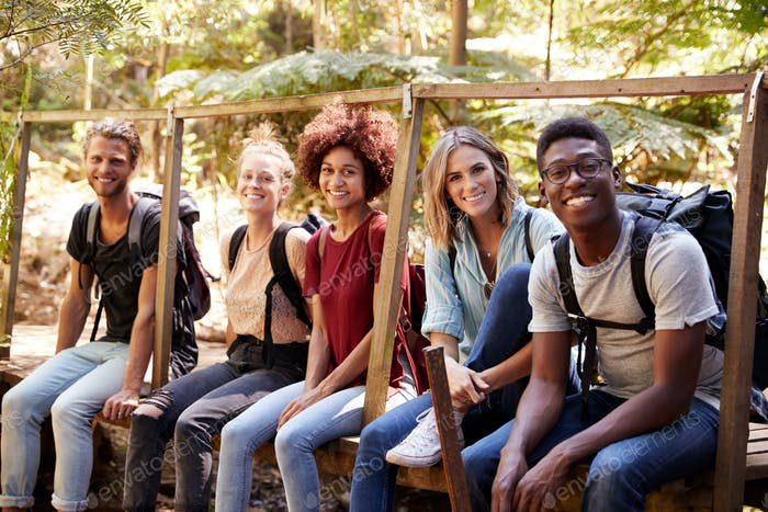 Five young adult friends on a hike sitting together smiling to camera during a break, close up