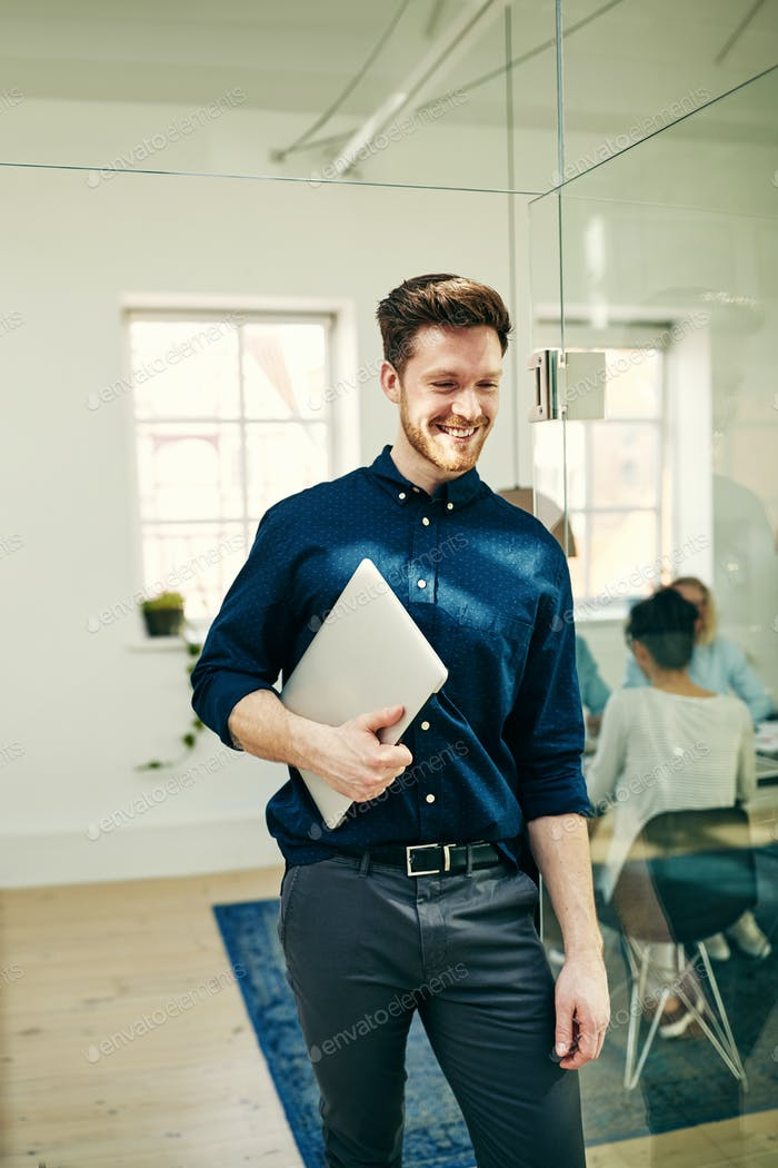 Smiling young businessman walking in an office carrying a laptop