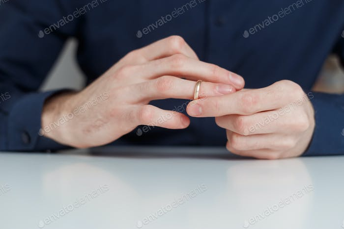 Young man is taking off the wedding ring. Close up view. Divorce concept