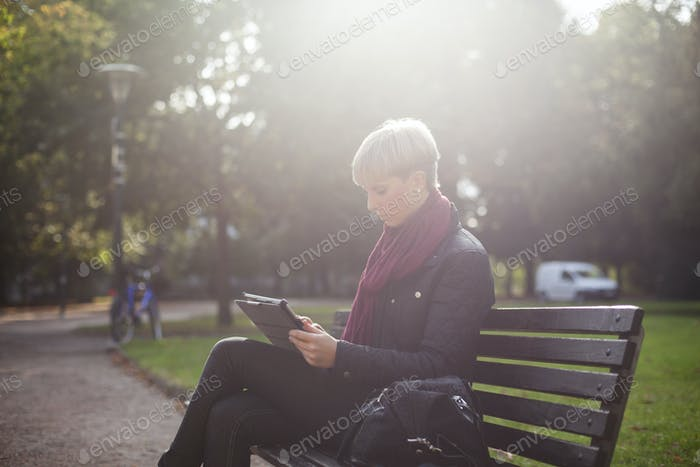 Woman sitting on bench while using digital tablet at university campus