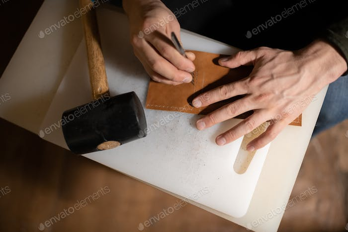 Cropped artisan creating ornament on leather handicraft