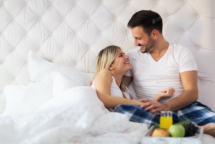 Romantic happy couple having breakfast in bed