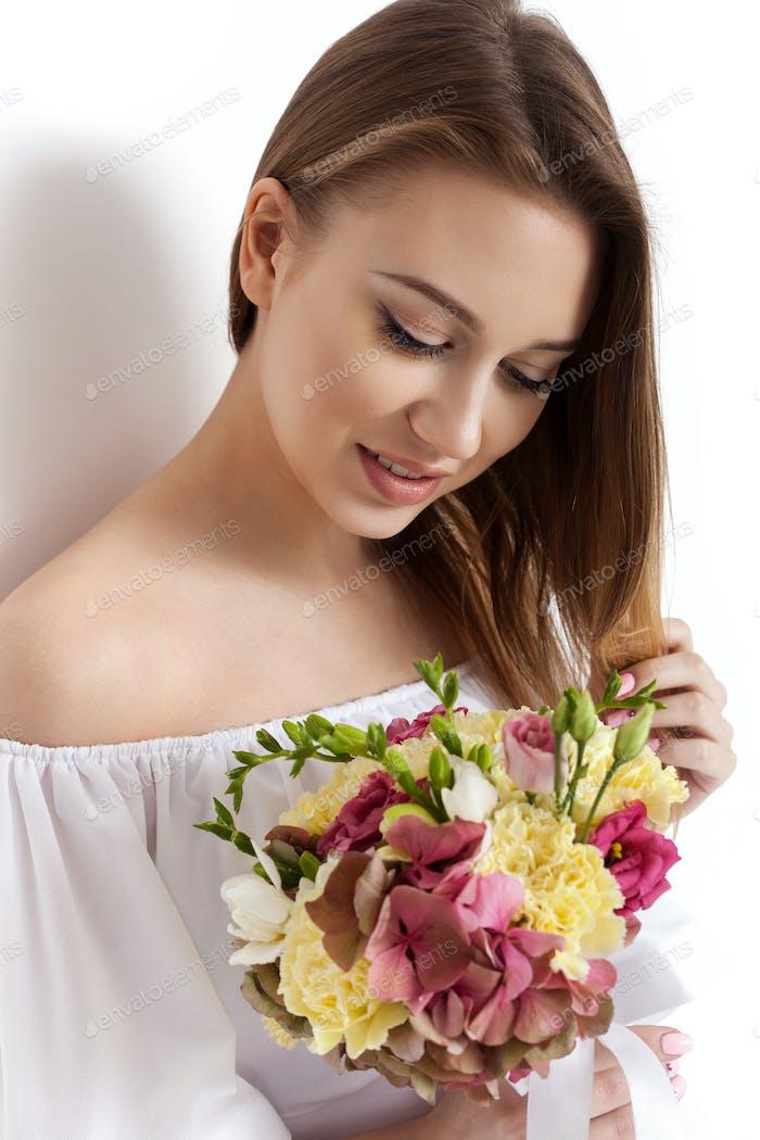 Happy surprised model woman smelling flowers