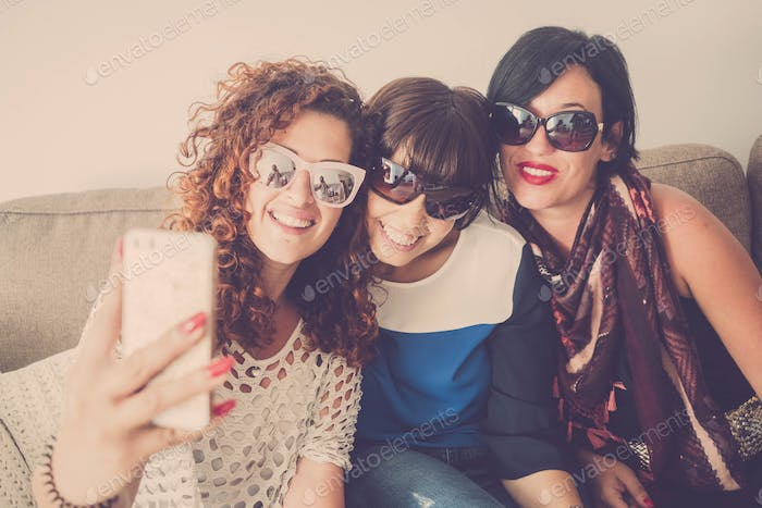 Three female friends at home use modern cellular phone