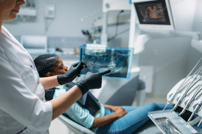 Female dentist shows problem on x-ray picture