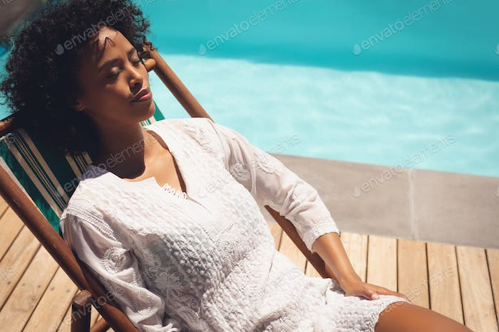 Close-up of African American woman relaxing on sun lounger in her backyard on a sunny day