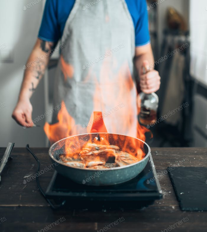 Chef against frying pan with fire, fish cooking
