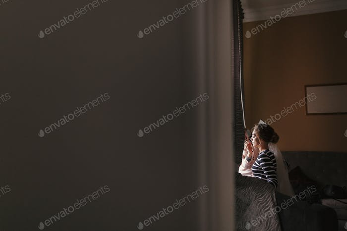 Makeup artist doing brows and applying eyeshadow on bride face
