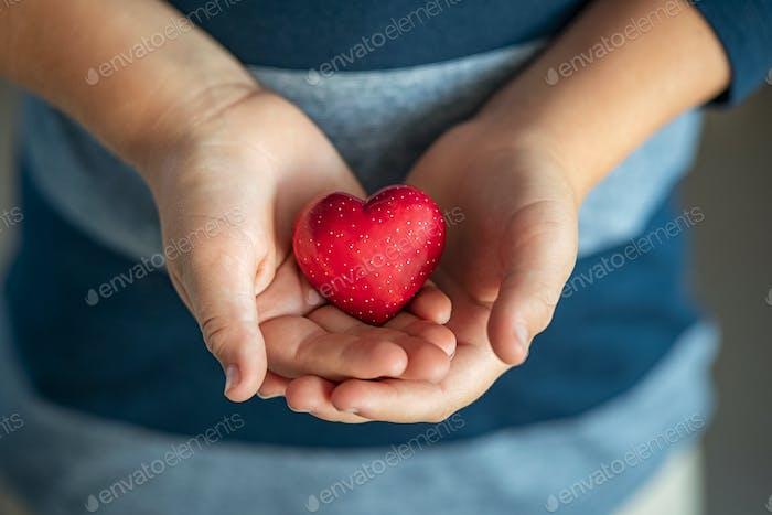 Kind hält rotes Herz in seinen kleinen Händen