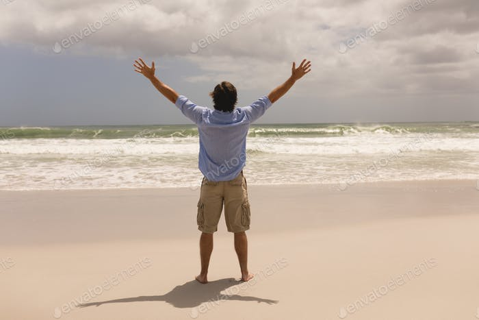 Caucasian man standing with arms outstretched on the beach