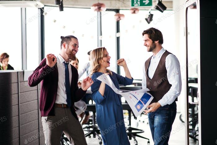Eine Gruppe von Geschäftsleuten, die in einem Büro stehen und Aufregung zum Ausdruck bringen