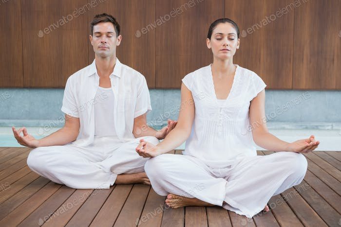 Attractive couple in white meditating in lotus pose in health spa