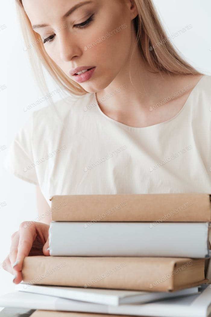 Serious blonde woman holding books. Looking aside.