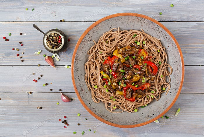 Stir fry from chicken hearts, paprika, onions and buckwheat noodles. Top view