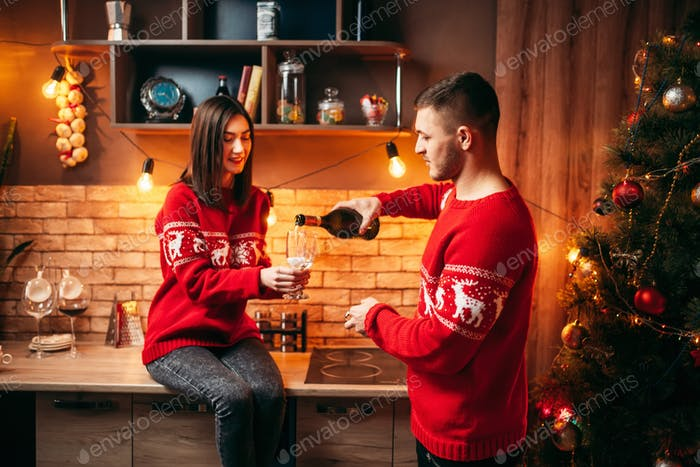 Couple, man pours champagne in a glass, christmas