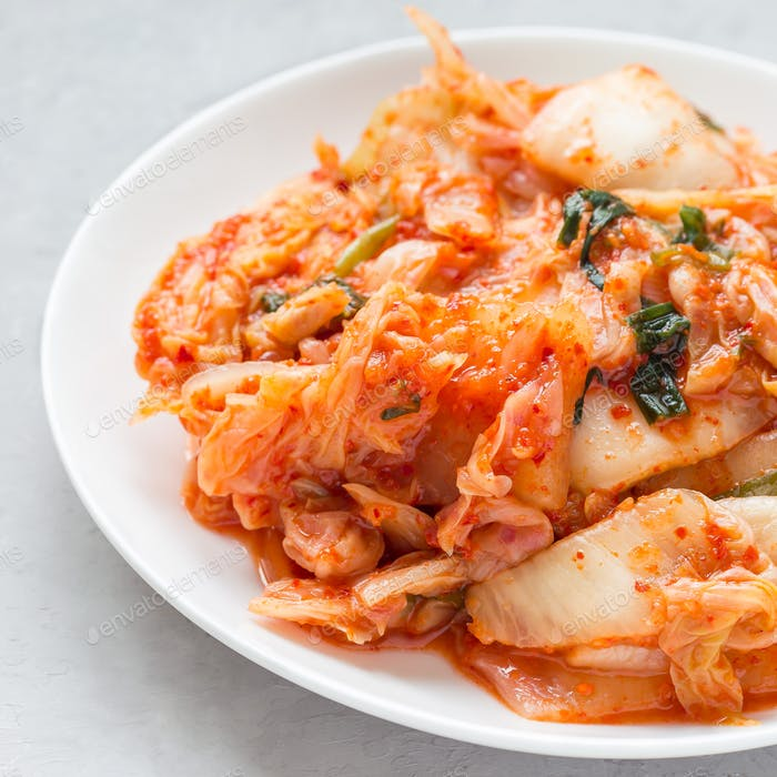 Kimchi cabbage. Korean appetizer on a white plate, square