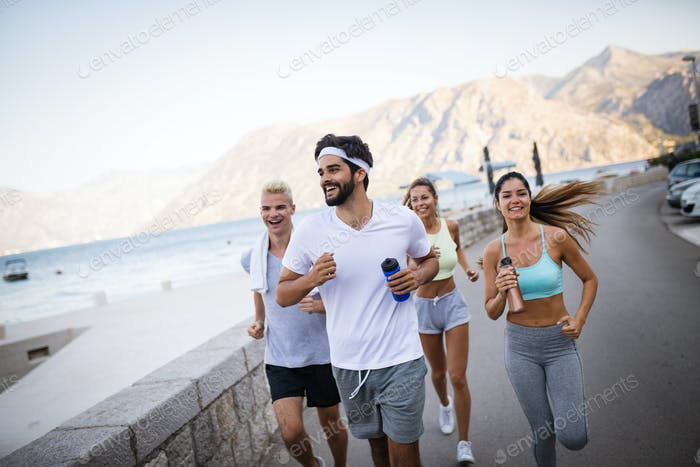 Group of young people jogging and running outdoors in nature