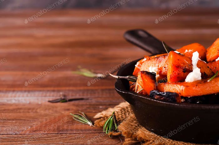 Roasted, baked pumpkin with addition aromatic herbs and goat cheese