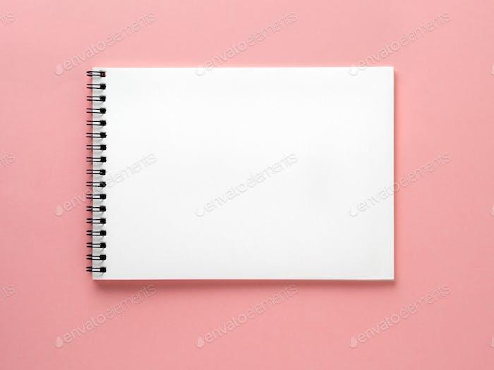 Leere Notizblock weiße Seite auf rosa Schreibtisch, farbiger Hintergrund. Draufsicht, flach gelegt.