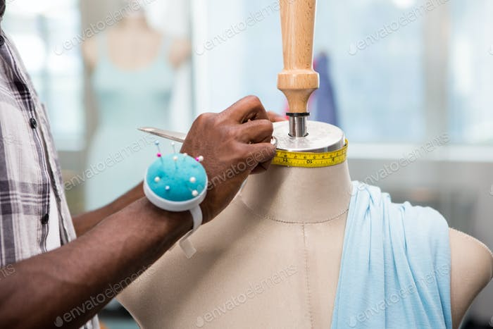 Close up of male fashion designer and mannequin