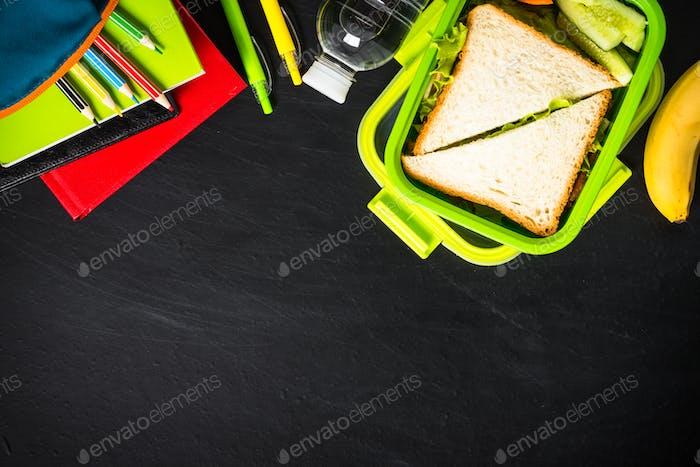 Zurück zum Schulkonzept. Brotdose mit Schreibwaren auf schwarz