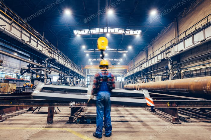 Blue-collar worker operating crane hook in a big factory.